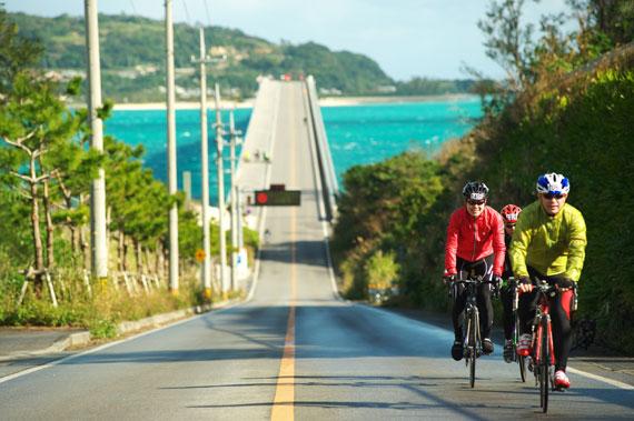 사이클 선수들이 일본 오키나와의 고우리대교를 건너 언덕을 오르고 있다.