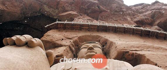 중국 간쑤성 황하 상류 병령사 계곡에 눈꽃이 날린다. 높이 27m짜리 대불(大佛) 머리 위에 나무로 만든 잔교(棧橋)가 아슬아슬하게 걸려 있다. 석굴 벽화와 불상을 보기 위해선 잔교가 유일한 통로다.