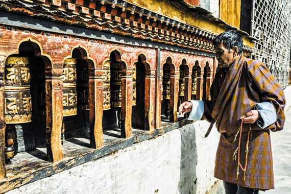 팀푸의 창강카 사찰서 기도하며 기도의 바퀴를 돌리고 있는 노인.