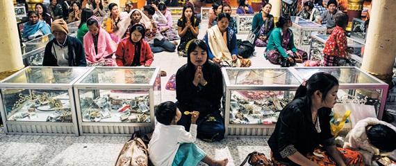 성지 순례 온 미얀마 사람들이 골든 록 앞에서 기도를 드리고 있다.