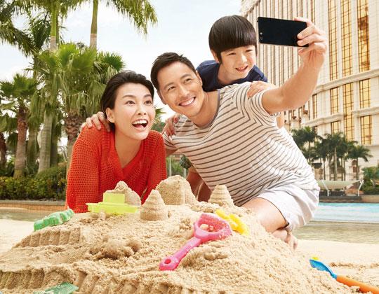 갤럭시 마카오 풀장에서 모래성 쌓기 놀이를 하고 있는 가족.