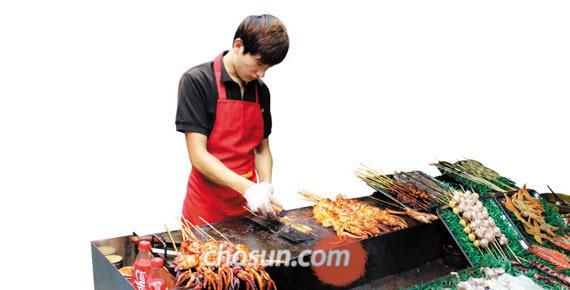 중국 칭다오시의 전통음식 거리 피차이위앤에서 한 상인이 오징어꼬치(카오요우위)를 굽고 있다.